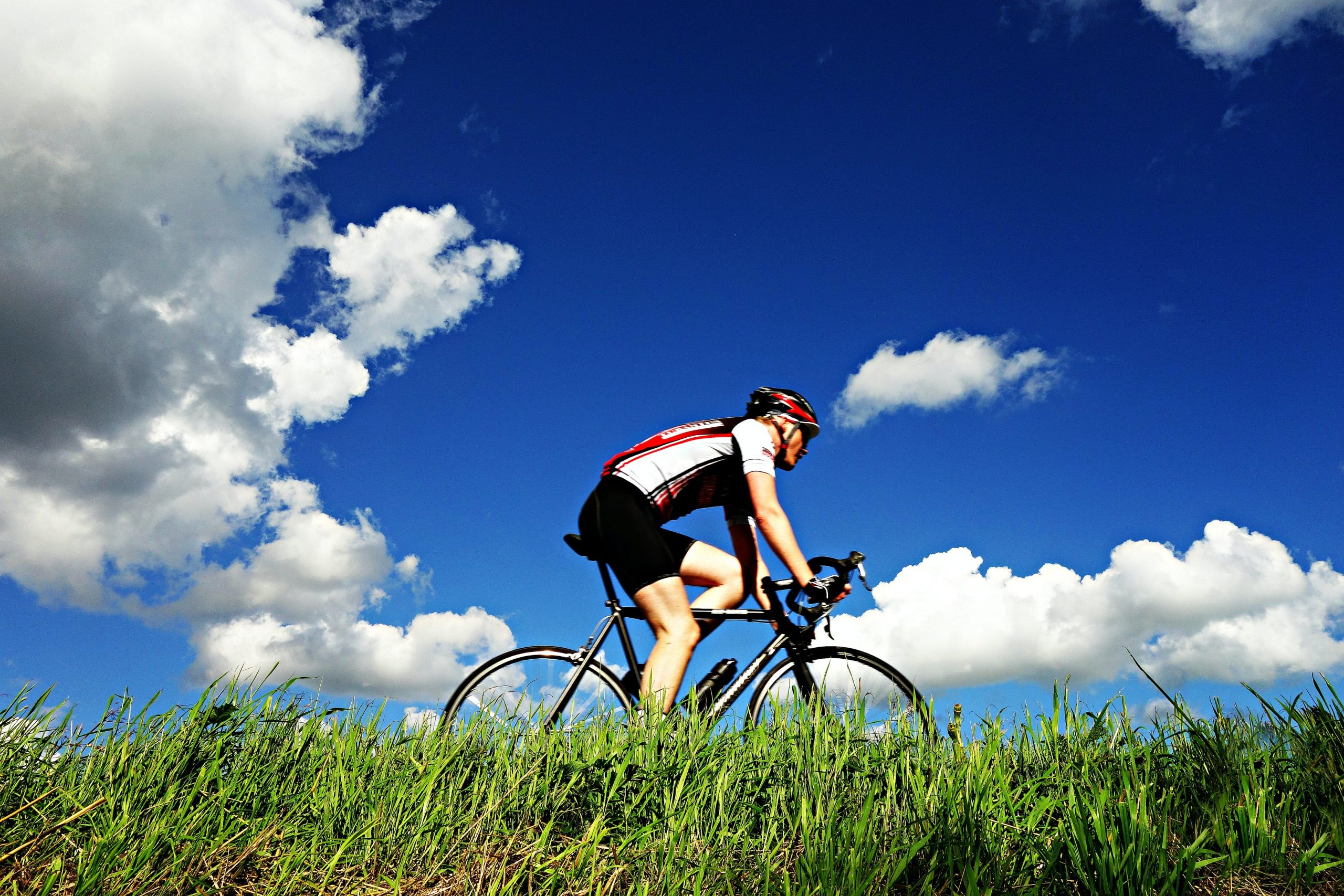 Image of a man cycling, with a blue cloudy sky in the background.