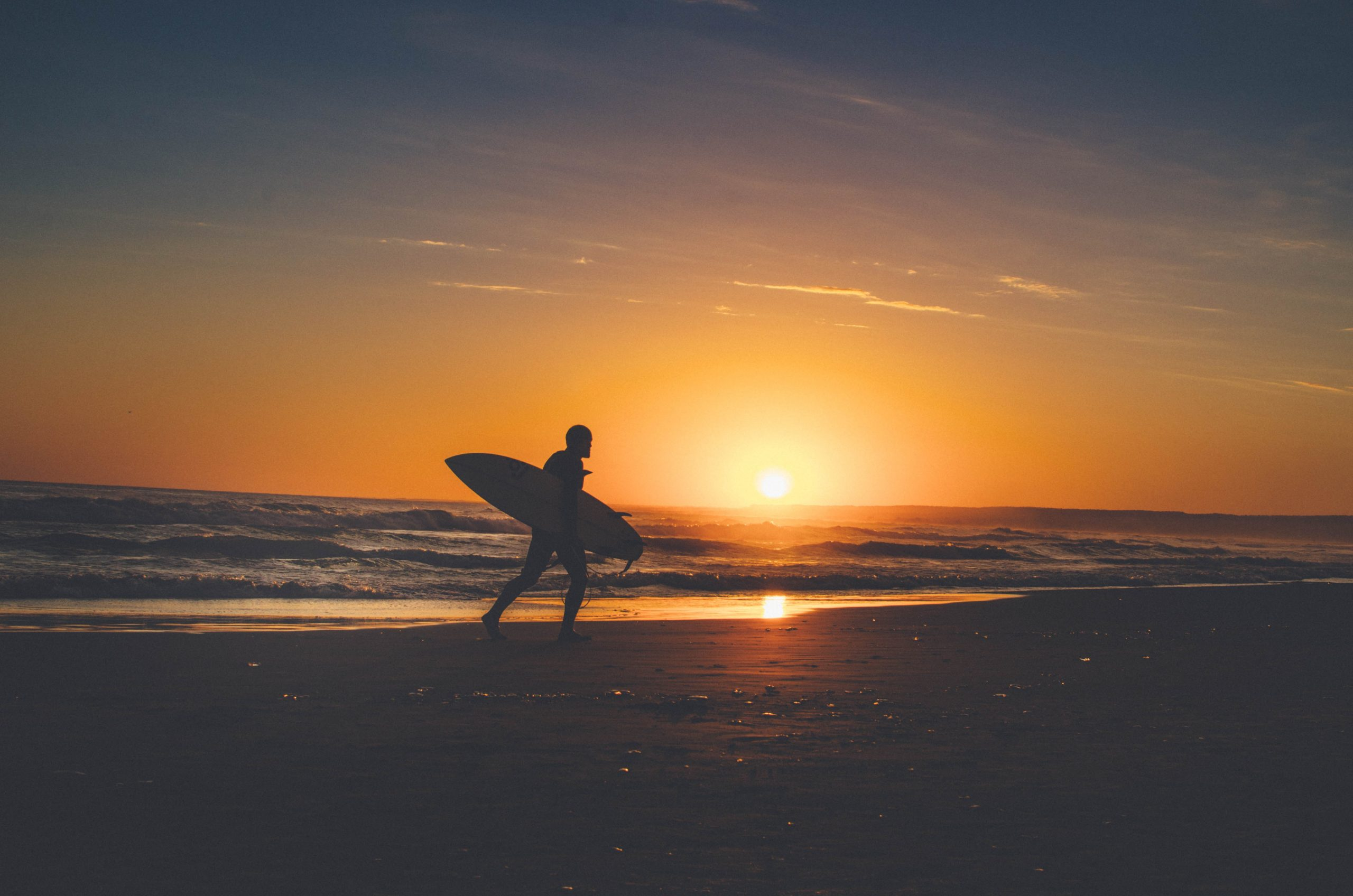 A surfer holding a surfboard and walking along the shore at sunset.