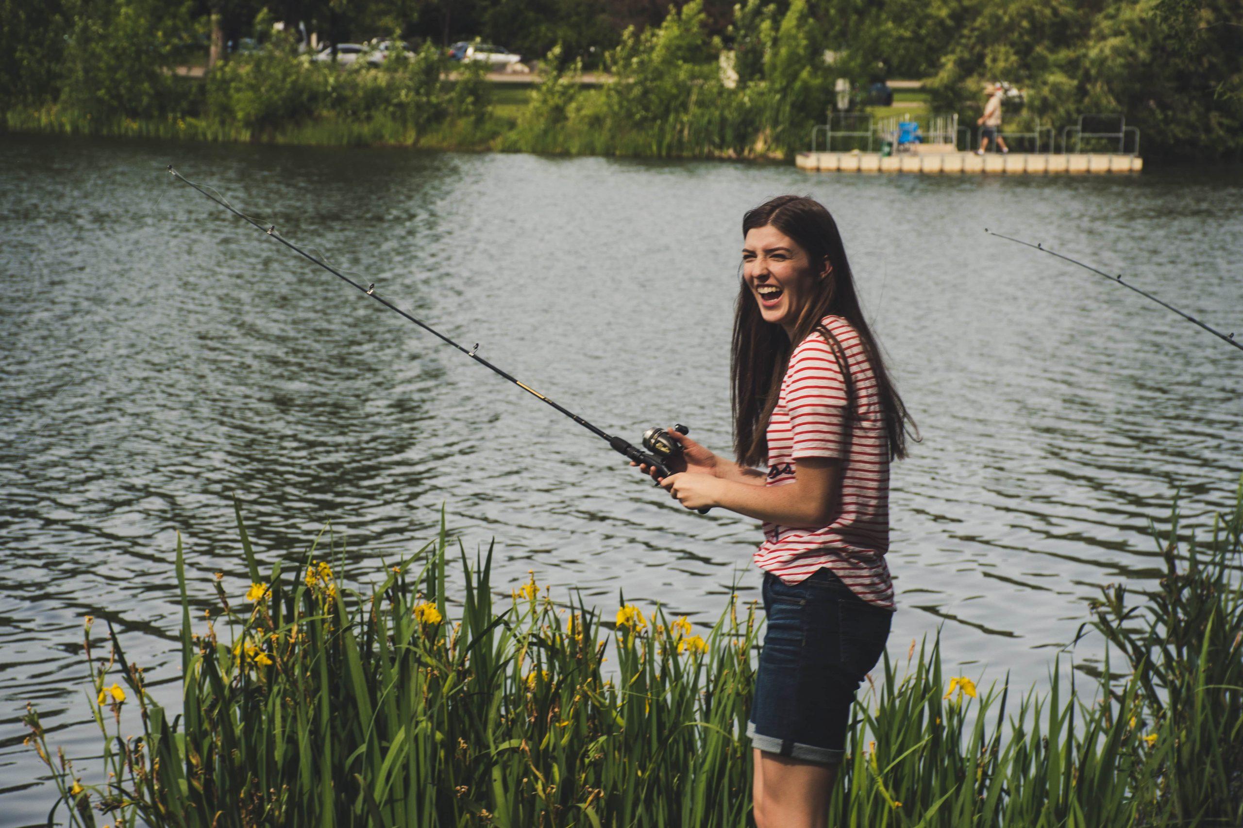 Image of a woman fishing at a lake.