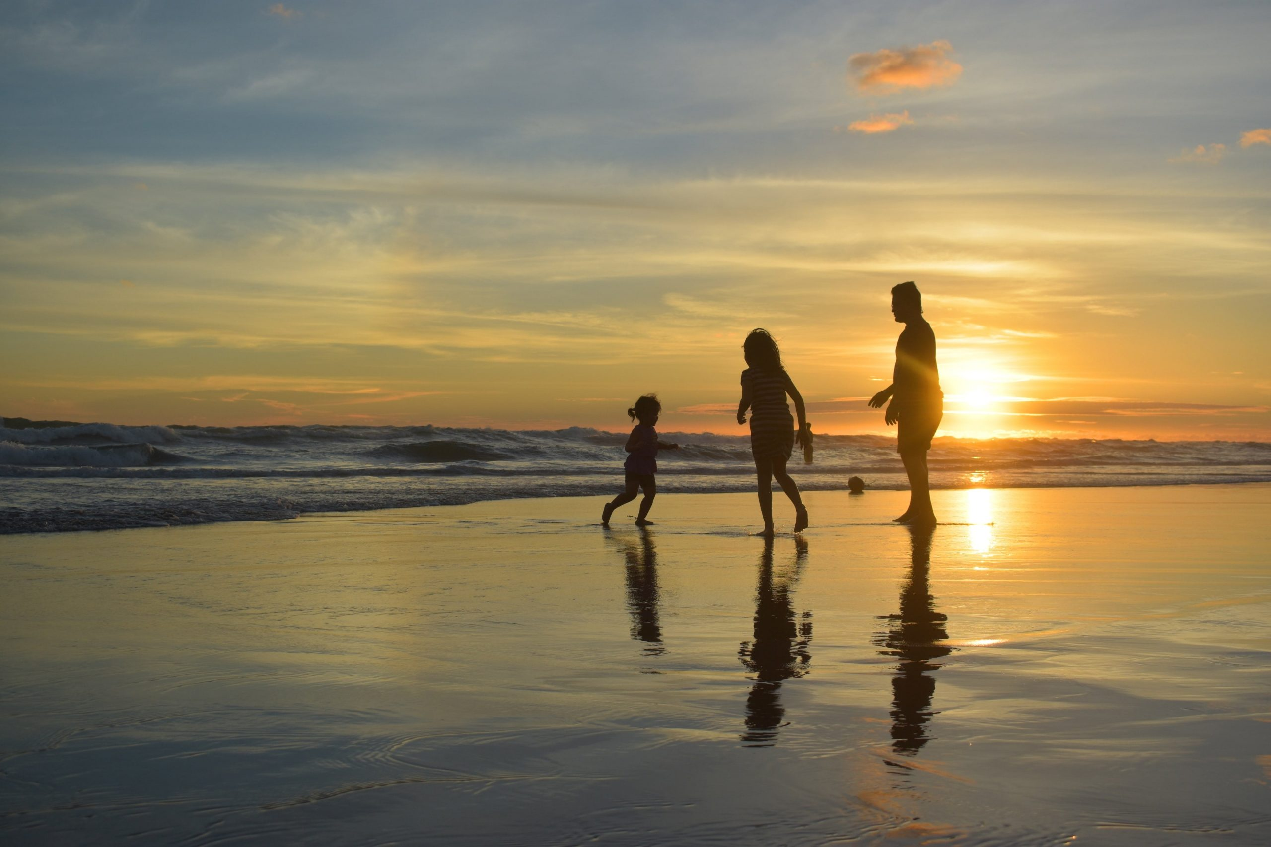 Image of a family of three, walking on the beach at sunset.