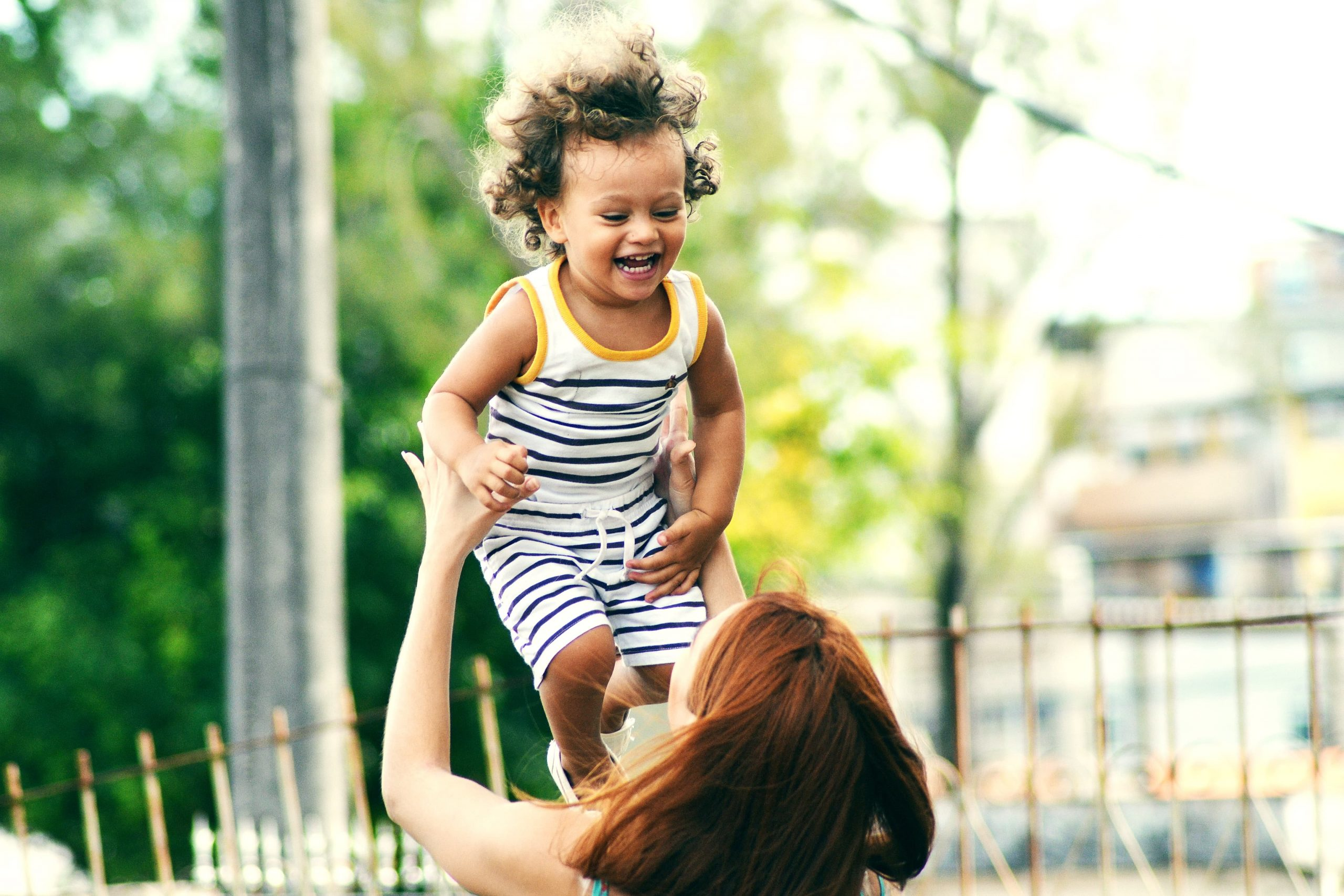 Image of a dark haired mother holding her curly haired child in the air.