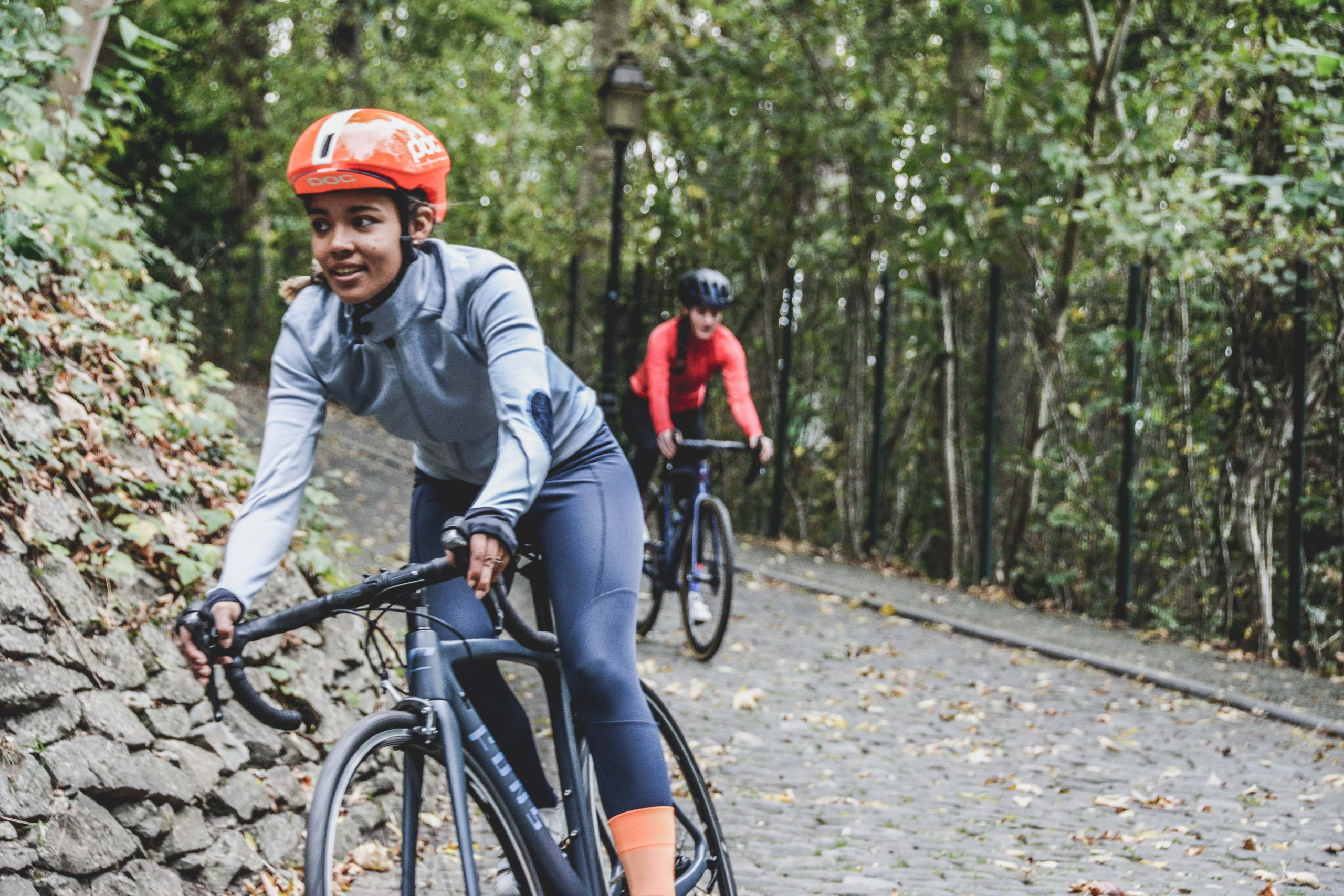 Image of a man and a woman cycling through a woodland trail.
