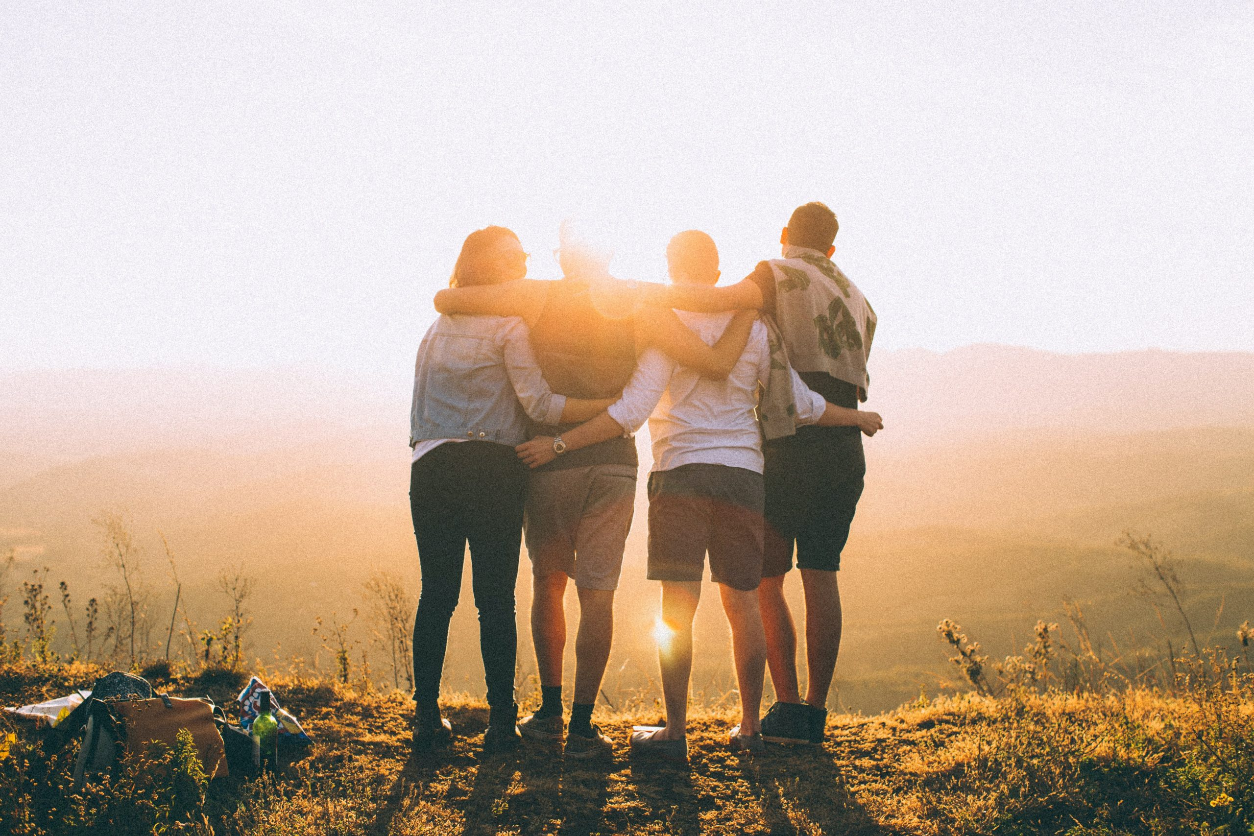 Image of the back of a group of four people with their arms around each other at sunset.